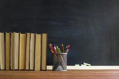 Manuali e rifornimenti di scuola su una tavola, contro un fondo della lavagna con gesso Concetto della scuola con il copyspase Fotografia Stock Libera da Diritti