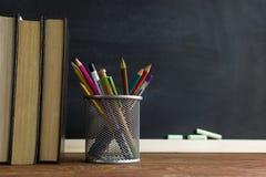 Manuali e rifornimenti di scuola su una tavola, contro un fondo della lavagna con gesso Concetto della scuola con il copyspase Fotografie Stock