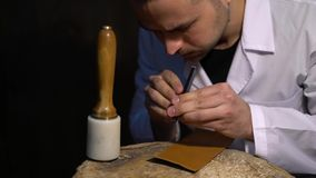 Manually cutting of skin during craft manufacturing leather goods. Workshop of skinner, close-up shot showing hands of. Master and production process stock video footage
