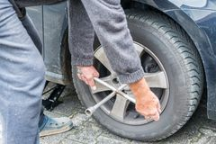 Manually tire change with four-way socket wrench stock image