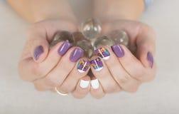 Manucure élégante lumineuse avec les globes en verre se tenants polonais colorés de gel d'ongle Photo libre de droits