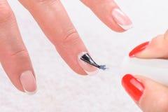 Manucure, appliquant l'émail clair Photo stock