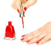Manucure appliquant le vernis à ongles rouge photographie stock libre de droits