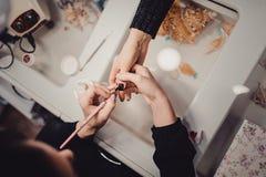 Manucure dans le salon de beauté Foyer sélectif sur la brosse Photos stock