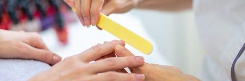 Manucure employant le dossier d'ongle pour former des ongles de doigt images stock