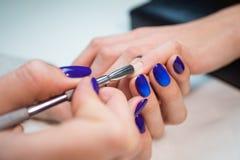 Manucure enlevant la cuticle du clou de fille Images stock