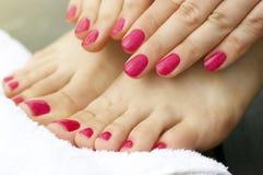 Manucure et pédicurie roses sur les mains et les jambes femelles, plan rapproché, vue de côté photos stock