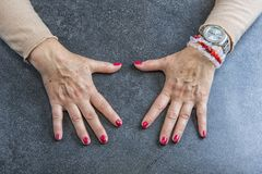 manucure Mains de dame âgée polissant des ongles avec le vernis à ongles rouge dans le salon de beauté photo libre de droits