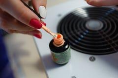 Manucure principale, brosse d'ongle d'immersions dans un ongle orange de gel de couleur de pot Images libres de droits