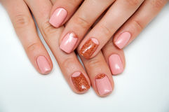 Manucure rose d'or sur les ongles carrés courts Photographie stock