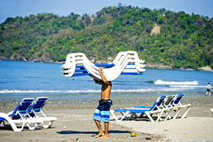 Manuel Antonio beach, Costa Rica. Manuel Antonio, Costa Rica - February 26, 2014: A man brings and sets up chairs for beach goers royalty free stock photo
