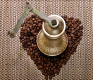 Manuel grinder with coffe beans. Manuel grinder with coffee beans on a bamboo background Stock Photography