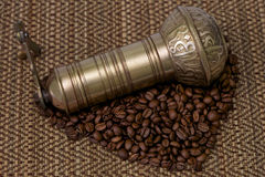 Manuel grinder with coffe beans. Manuel grinder with coffee beans on a bamboo background Stock Images