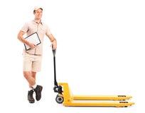 Manuell arbetare bredvid en gaffelpalettlastbil Arkivfoton