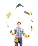 Manuell arbetare som jonglerar med hjälpmedel Fotografering för Bildbyråer