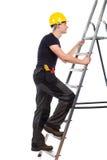 Manuell arbetare som klättrar en stege royaltyfria foton
