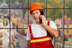 Manuell arbetare som talar på mobiltelefonen arkivfoton