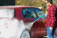 Manuell biltvätt med tryckvatten i biltvätt utanför E Lokalvårdbil genom att använda högtryckvatten fotografering för bildbyråer