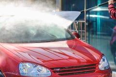 Manuell biltvätt med tryckvatten i biltvätt utanför E Lokalvårdbil genom att använda högtryckvatten royaltyfri foto