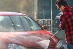 Manuell biltvätt med tryckvatten i biltvätt utanför E Lokalvårdbil genom att använda högtryckvatten royaltyfri fotografi