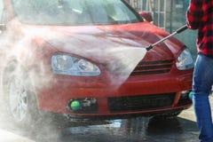 Manuell biltvätt med tryckvatten i biltvätt utanför E Lokalvårdbil genom att använda högtryckvatten arkivbilder