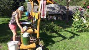 Manuell handtvätteriwash i bunke av den fattiga bondaktiga kvinnan i lantgårdhusgård 4K lager videofilmer