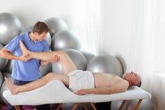 Manuell terapi - böjande manligt tålmodigt knä för ung fysioterapeut under massage royaltyfri foto