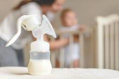 Manuelle Brustpumpe und -flasche mit Muttermilch auf dem Hintergrund der Mutter und des Babys nahe dem Baby ` s gehen zu Bett lizenzfreies stockfoto
