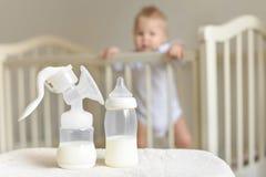 Manuelle Brustpumpe und -flasche mit Muttermilch auf dem Hintergrund des kleinen Babys im Bett lizenzfreies stockfoto