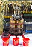 Manuelle Traubenpressenmaschine an mit drei roten Eimern stockfotografie