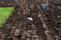 Manueller Eisenpflug, -schaufel und -eimer im Boden, auf dem Landwirtgebiet Lizenzfreies Stockfoto