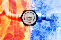 Manueller Heizungsprüfer mit den roten und blauen Pfeilen im Feuer- und Eishintergrund Stockfotografie