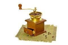Manueller Kaffeeschleifer und Kaffeebohnen auf Segeltuch. Stockfoto