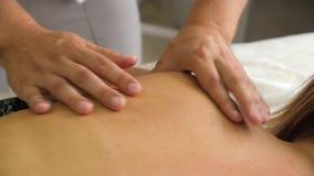 Manueller Therapeut, der eine junge Frau liegt auf einer Massagetabelle, drückend auf die Rückseite massiert Männliches Masseurha stock video footage