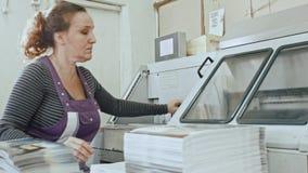 Manuellt arbete - polygrafprintingprocess - en kvinna avslutar ett papper för en tidskrift arkivfilmer