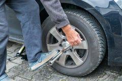 Manuellt gummihjuländring med fyrvägshålighetskiftnyckeln Arkivfoton