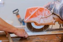 Manuellt klipp av keramiska tegelplattor på en special maskin för att klippa tegelplattor fotografering för bildbyråer
