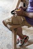 Manuellt träbegrepp Profilsidosikten kantjusterade fotoet av möbelsnickaren som faktotumet sitter i garage eller arbetsrum på en  arkivfoto