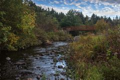 Manuels River walking trail. Bridge, Conception Bay South, Newfoundland and Labrador, Canada. Autumn colors on the river trail royalty free stock images