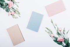 Manuels scolaires sur le fond blanc au centre du cadre floral photographie stock libre de droits