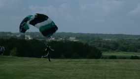 Manuevering the chute to land. A guy skillfully maneuvering his parachute to safely land in the open space where people are waiting for his safe return stock video