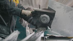 Manufacture of composite fiberglass reinforcement - worker cuts wires with circular saw. Telephoto stock video