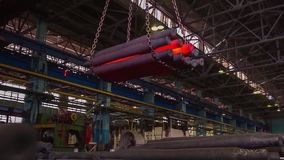 Manufacture of rails for trains and freight wagon, boxcars. Rail manufacturing plant. Stack of steel round bar - iron
