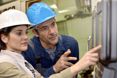 Manufacture workers setting up electronical machine. Manufacture workers working on electronic machine Stock Photo