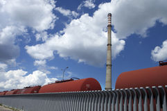 Manufactured landscape. Industrially manufactured landscape with vertical tall chimney and horizontal tank wagons line stock photography