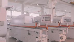 Manufactured woodworking machines stand in a row in stock. A large factory for the production of automated machine tools. Warehouse of woodworking machines stock footage