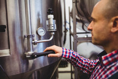Manufacturer adjusting pressure gauge in brewery Royalty Free Stock Photography