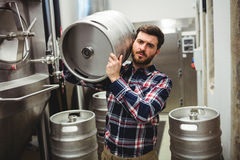 Manufacturer carrying keg in brewery Stock Photography