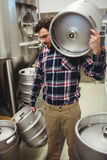 Manufacturer carrying kegs in brewery Royalty Free Stock Image
