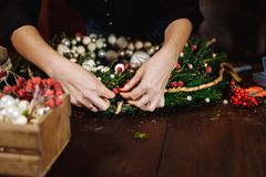 Young Cute smiling Woman designer preparing Christmas Evergreen Tree Wreath. Manufacturer of Christmas decor with their stock images